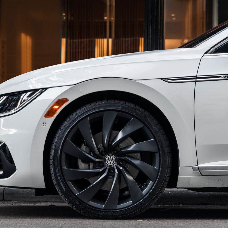 A pure white Volkswagen Arteon shows off its reflective black wheels in a cropped front driver's side silhouette.