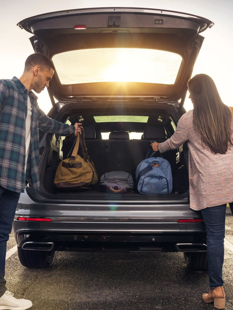 Young couple grabbing bags out of the trunk of their parked platinum gray metallic Volkswagen Tiguan in a park lot.