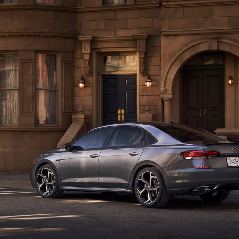 A platinum gray metallic Volkswagen Passat is parked off-street in front of neoclassical apartment building in early evening.