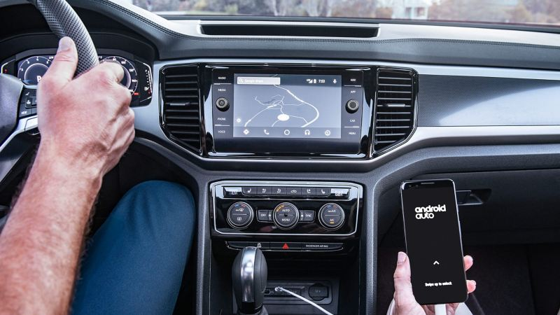 An interior dashboard view of the touchscreen navigation system shows a phone is plugged in and connected to Android Auto.