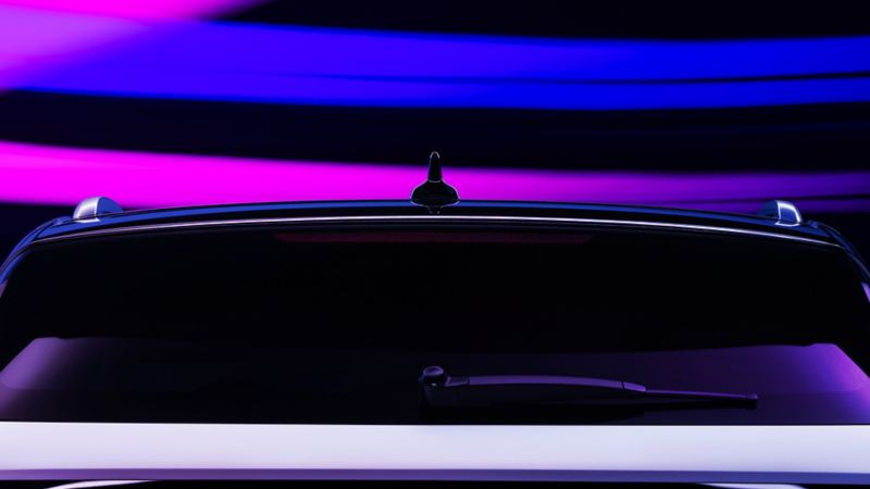 The brake lights of aVW ID.4 shown in Glacier White metallicare illuminated in the dark. Strokes of purple, pink and blue light add texture to the otherwise dark background.