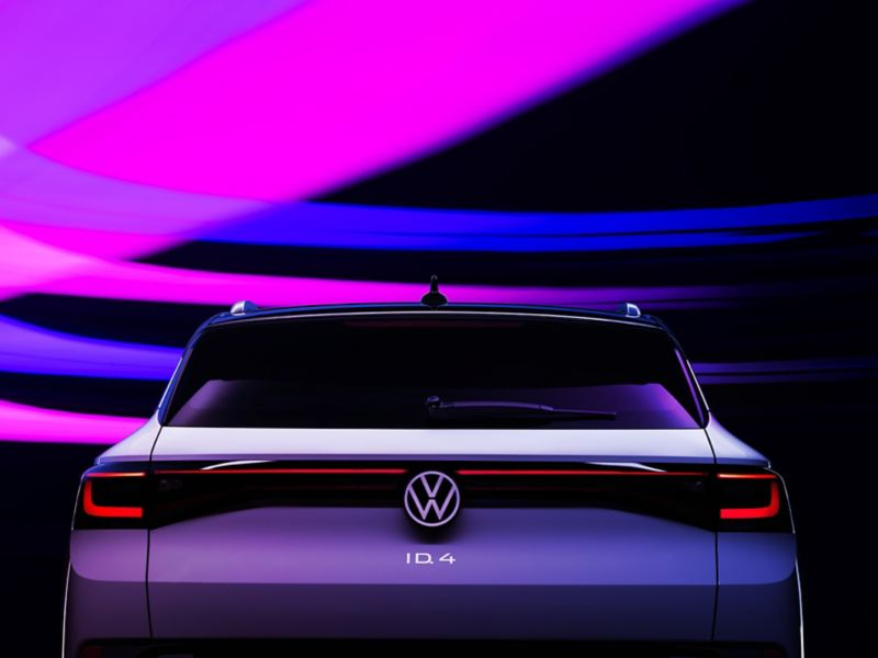 The brake lights of a VW ID.4 shown in Glacier White metallic are illuminated in the dark. Strokes of purple, pink and blue light add texture to the otherwise dark background.