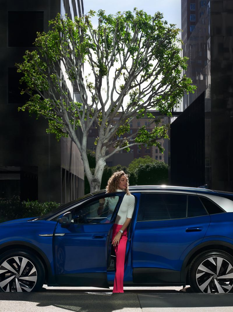 A woman climbs into the driver's seat of an ID.4, shown in Dusk Blue Metallic and parked on an urban street.