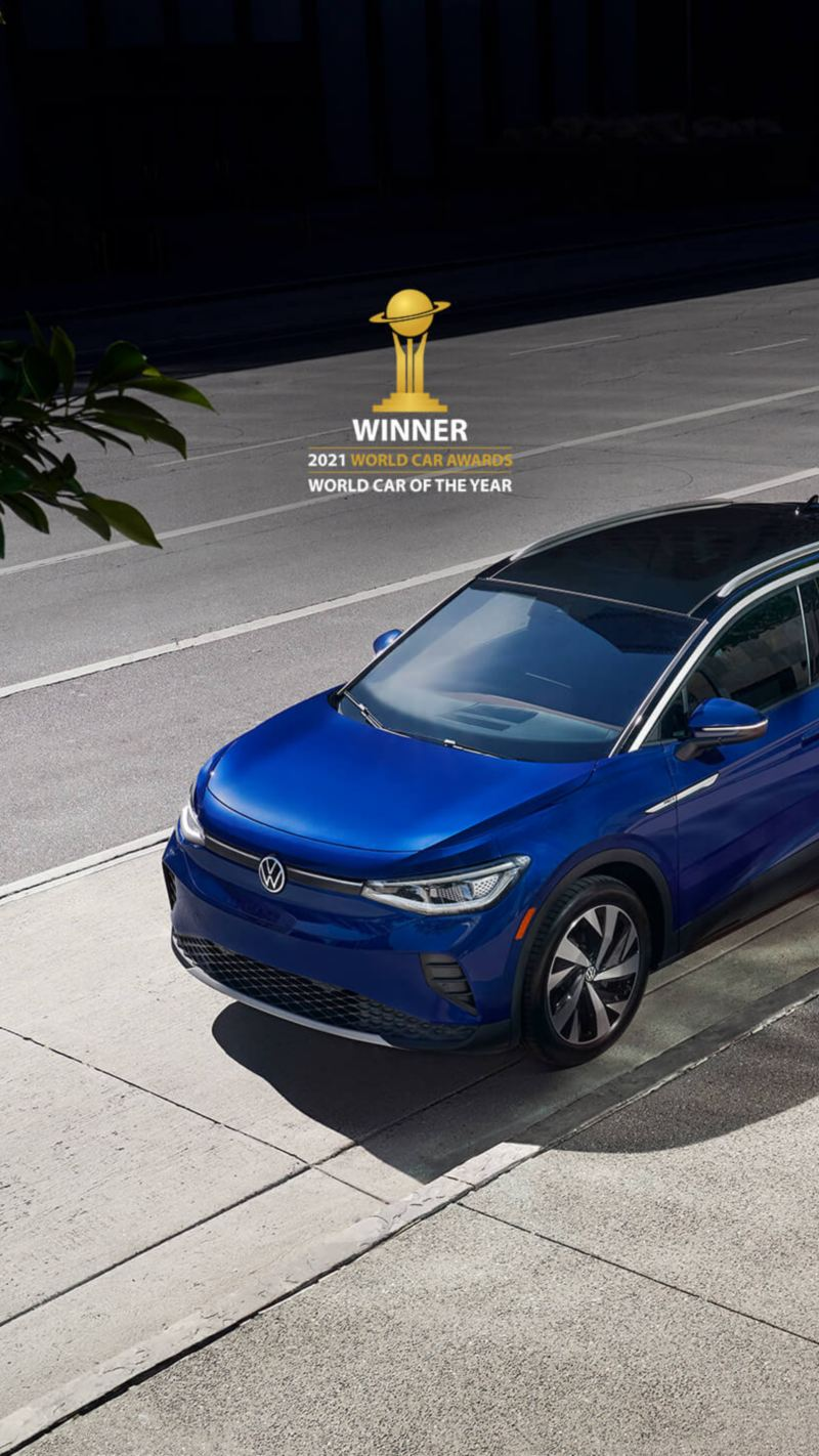 """Wide shot of a woman walking away from the driver's side of a parked ID.4 in Dusk Blue Metallic. Above the car sits a small version of the 2021 World Car Awards logo and type treatment that reads """"Winner"""" of """"World Car of the Year"""""""