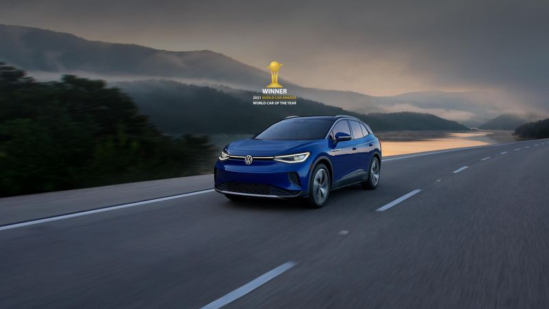 """A VW ID.4 EV in Metallic Dusk Blue drives on a two-lane highway with mountains in the background. Above the car sits a small version of the 2021 World Car Awards logo and type treatment that reads """"Winner"""" of """"World Car of the Year"""""""