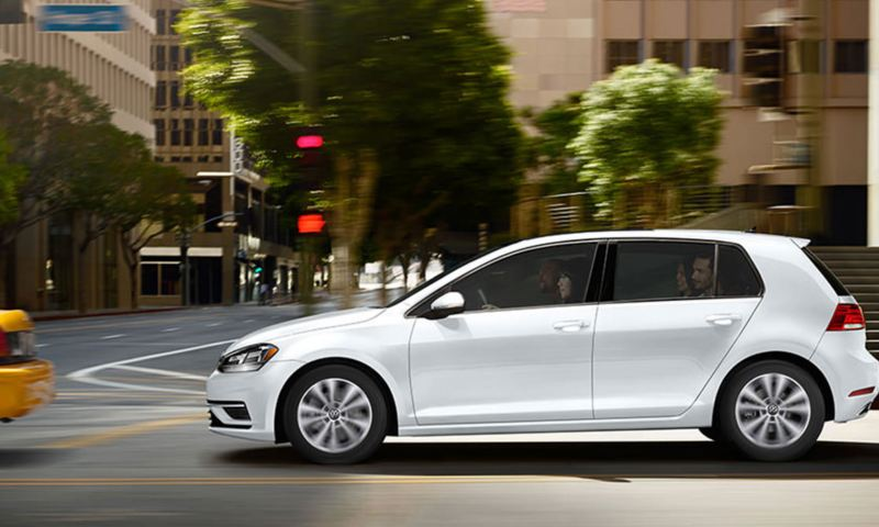 Pure White Golf TSI in motion on a city street.