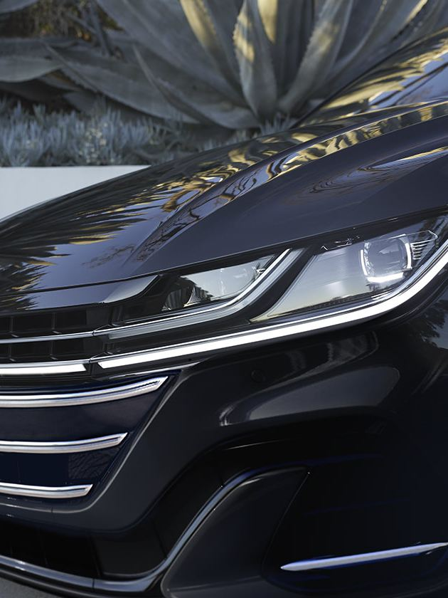 Arteon shown in Deep Black Pearl; front view of a LED headlight with Daytime Running Lights
