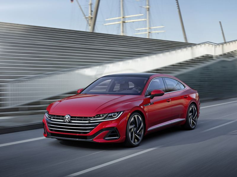 Arteon shown in Kings Red Metallic driving in front of modern wall and stairs