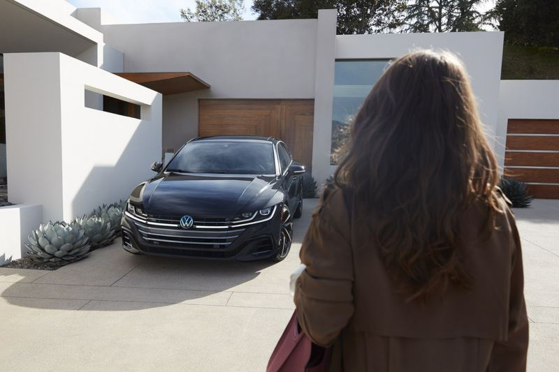 Arteon shown in Deep Black Pearl parked in the driveway of a modern home.