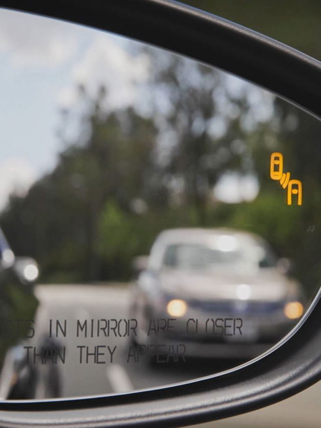 Blind spot mirror shows car advancing from behind