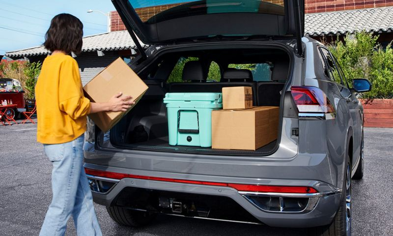 A woman places boxes inside the spacious trunk of a Pure Gray Atlas Cross Sport.