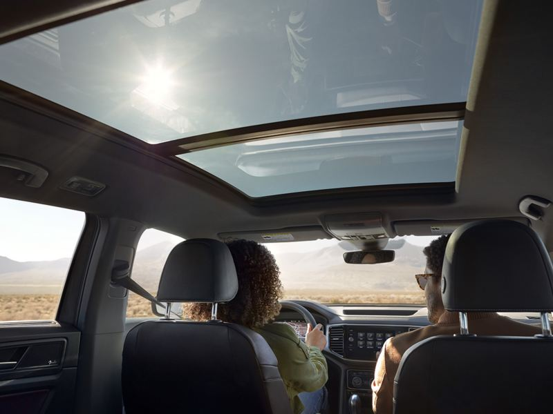 A driver and passenger inside the Atlas Cross Sport with the available panoramic sunroof.