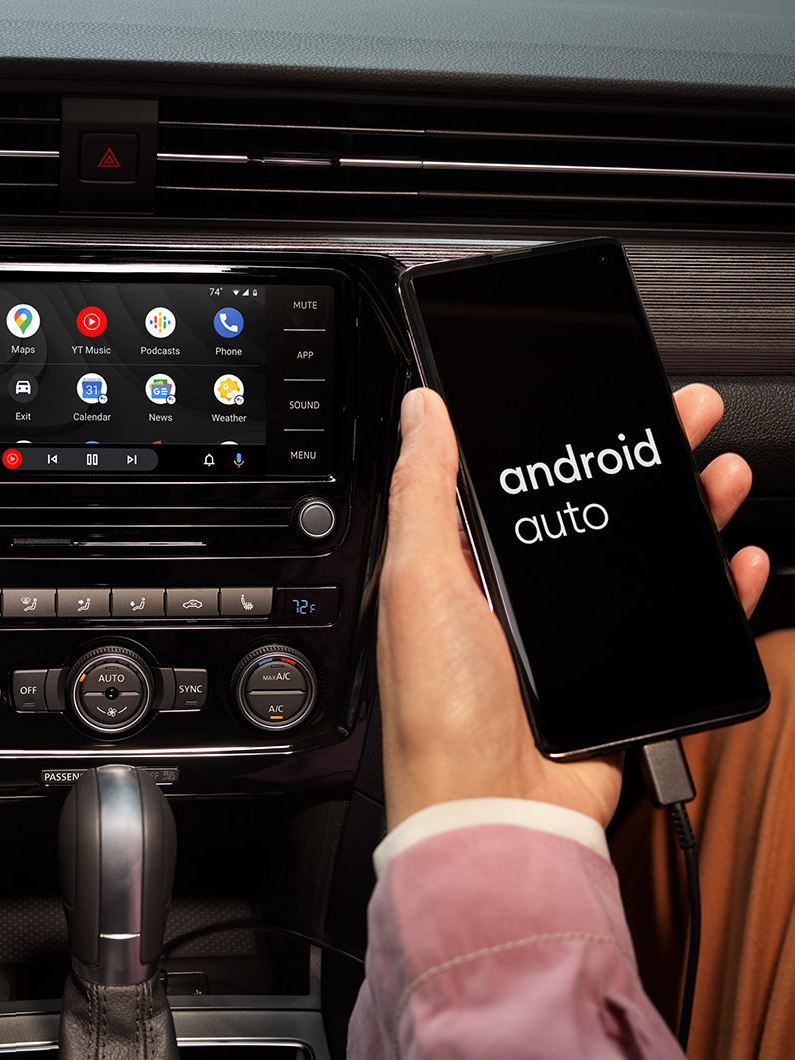 The hand of a person sitting in the front passenger seat of a Passat holds their Android phone as it's plugged in and connected to App-Connect.