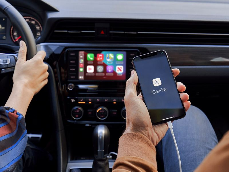 The hand of a person sitting in the front passenger seat of a VW Passat holds their iPhone as it's plugged in and connected to App-Connect.
