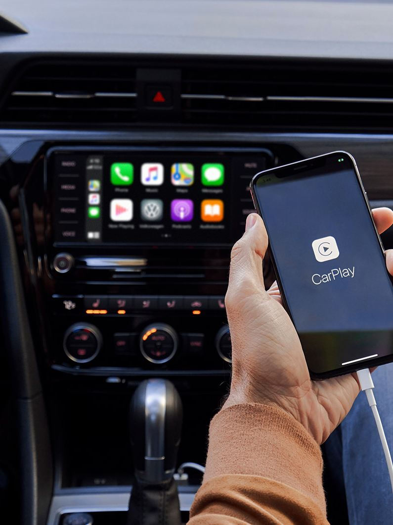 The hand of a person sitting in the front passenger seat of a VW Passat holds their iPhone as it's plugged in and connected to App-Connect