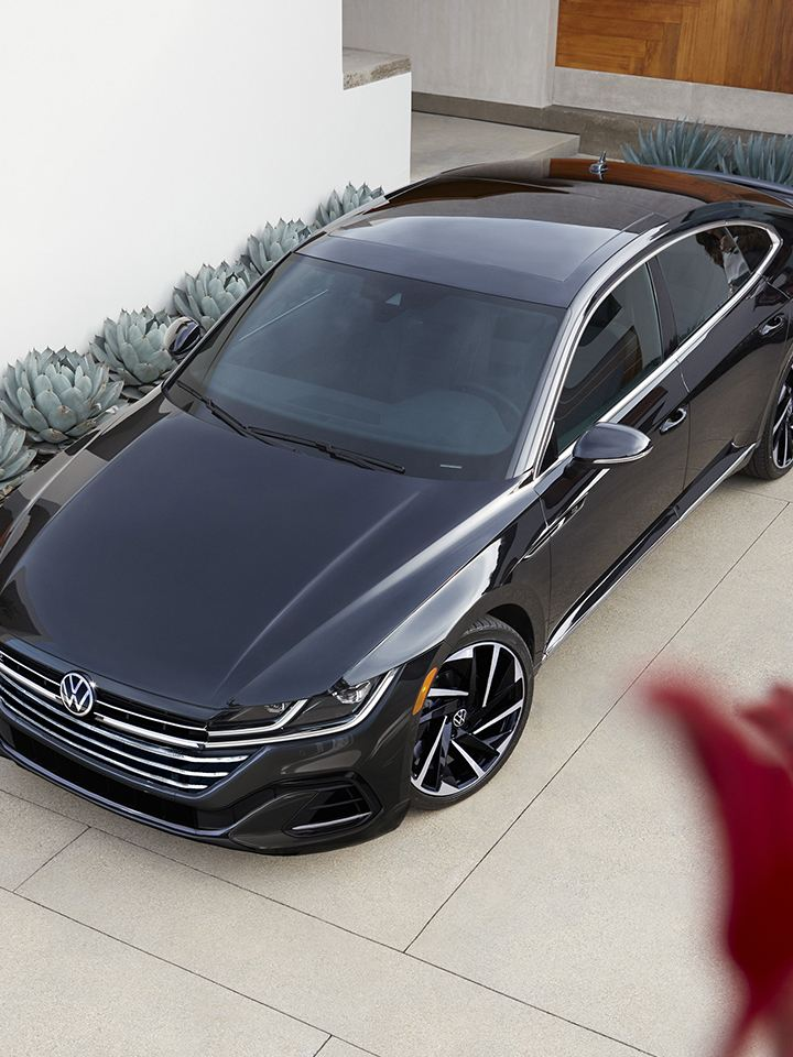 Arteon shown in Deep Black Pearl parked in the driveway of a modern home with woman walking to Arteon