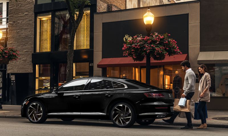 Arteon shown in Deep Black Pearl with man and woman at rear of Arteon