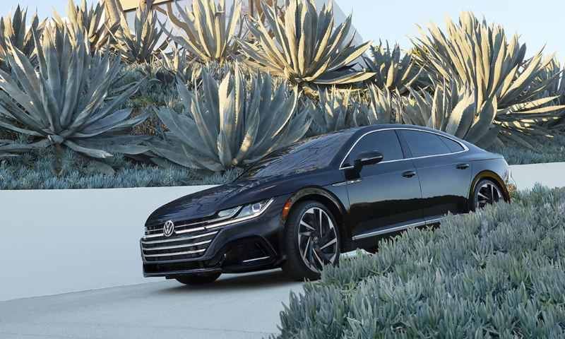 Arteon shown in Deep Black Pearl with LED headlights in front of house and garden.