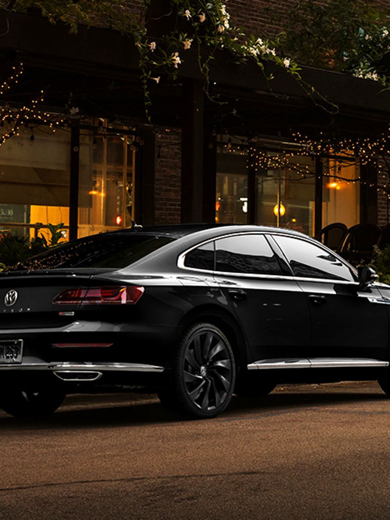 Arteon parked outside of an upscale restaurant at night.