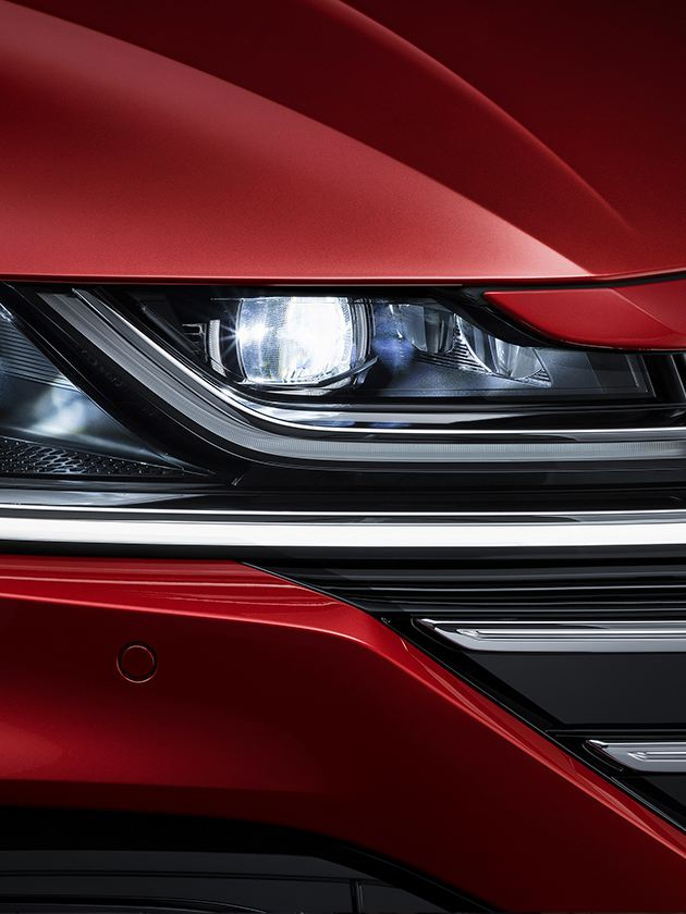 Arteon in Kings Red Metallic; front view of LED headlights with Daytime Running Lights
