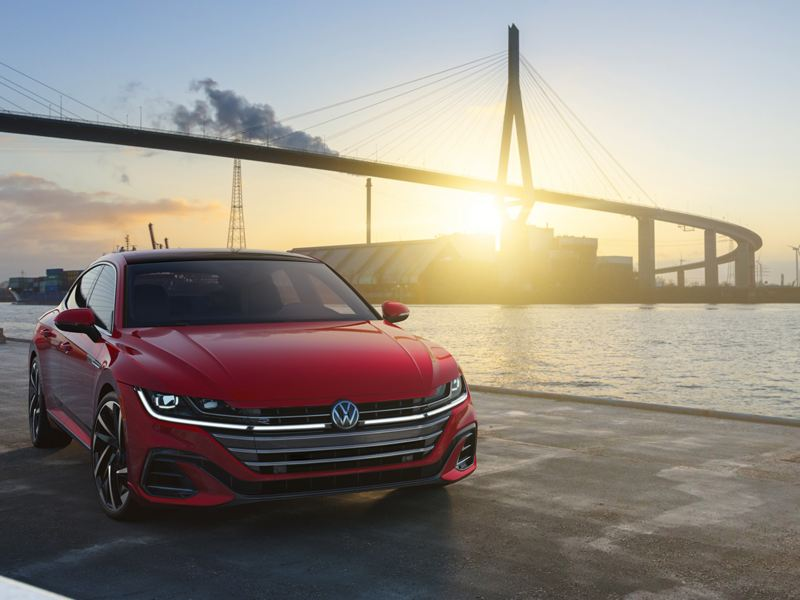 Arteon shown in Kings Red Metallic parked on waterfront with bridge in background