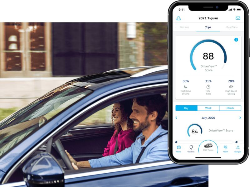A man is driving his VW, the in-app, VW Car-Net® Remote Access Drive View is displayed on a superimposed mobile phone.