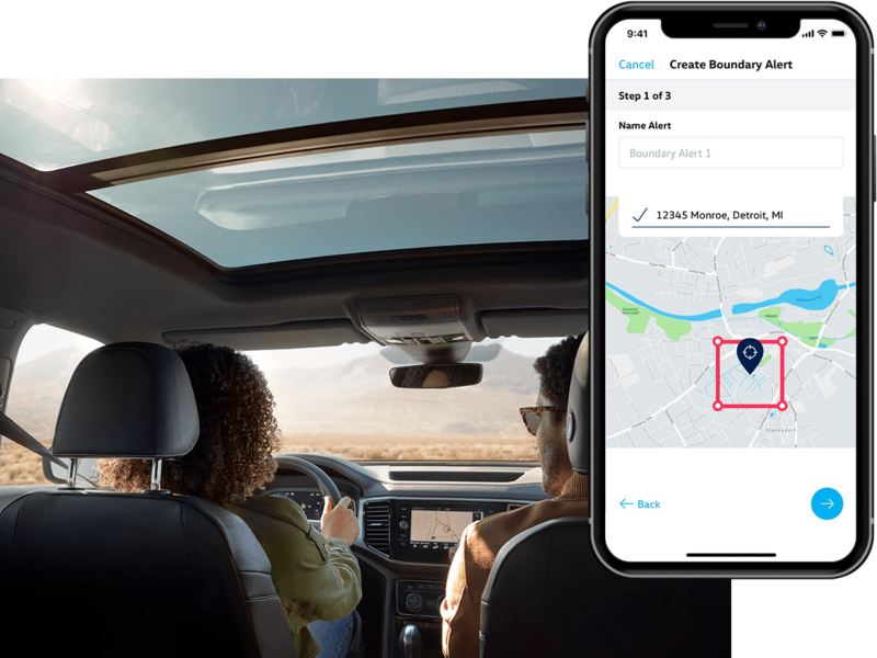 A man and woman review their Boundary Alert in their Car-Net app from their parked Volkswagen.