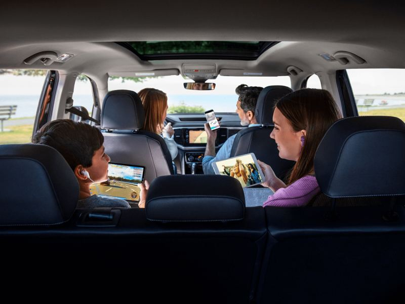 A family of four activates their Car-Net hotspot to use their handheld devices while parked at the coast.