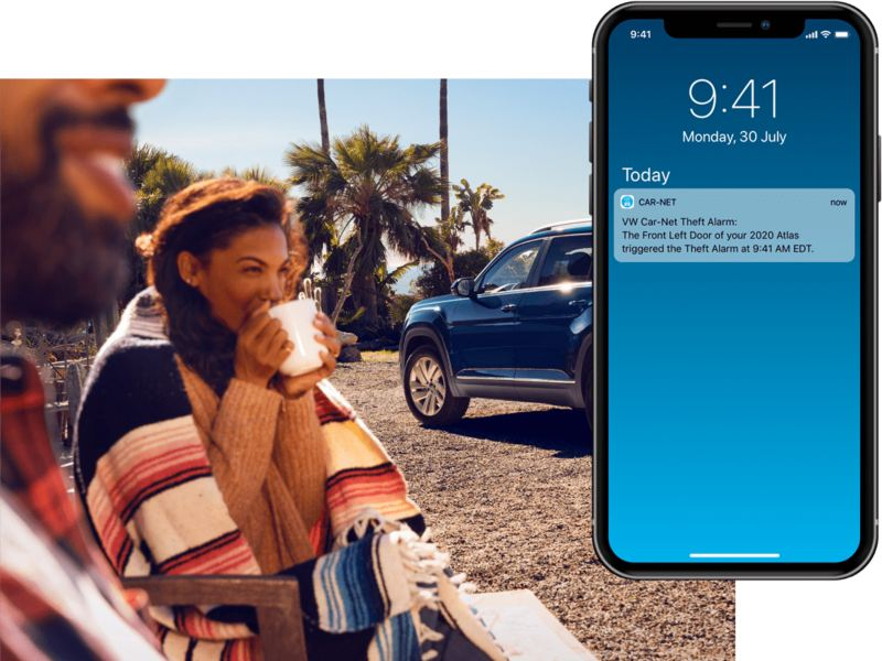 A man and women enjoy a mug of coffee outside their VW. On their mobile phone, we see a Volkswagen Car-Net® Safe & Secure alert.