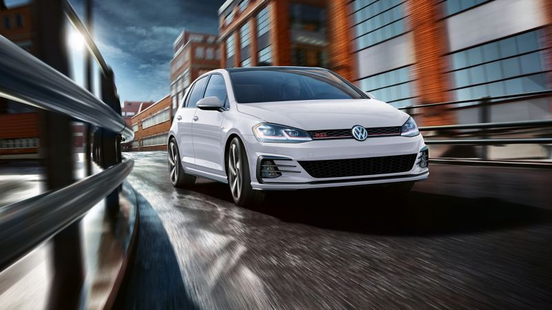 A Pure White Golf GTI drives along a city street during the daytime.