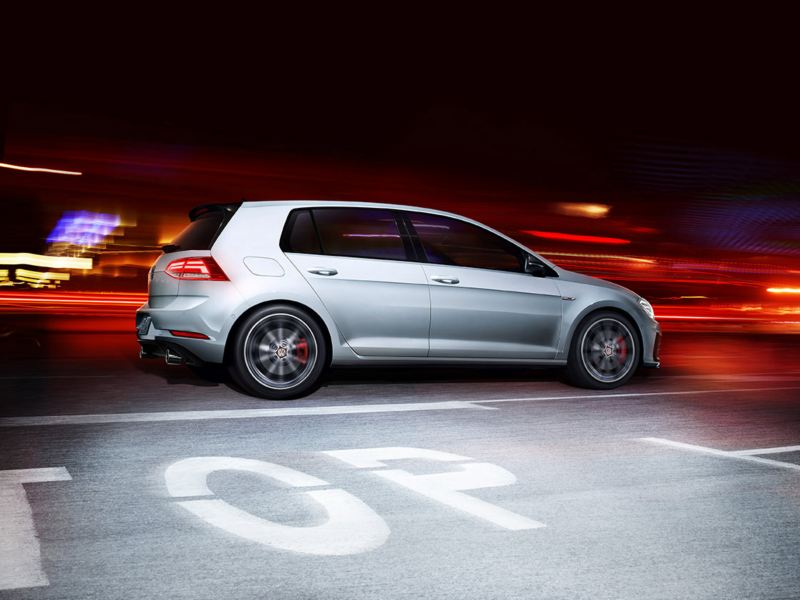 A side profile of a Golf GTI in White Silver Metallic as it's driving at night.
