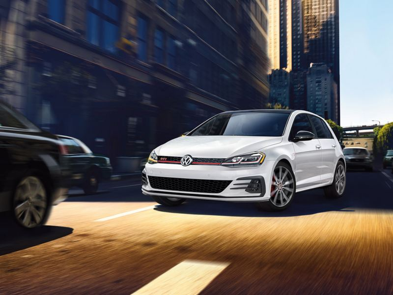 Golf GTI shown in White Silver Metallic driving though a city.