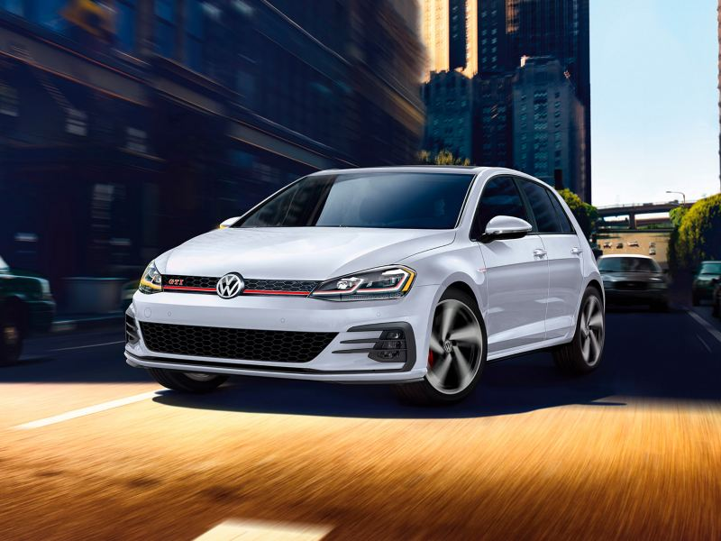 Pure White Golf GTI driving though a city