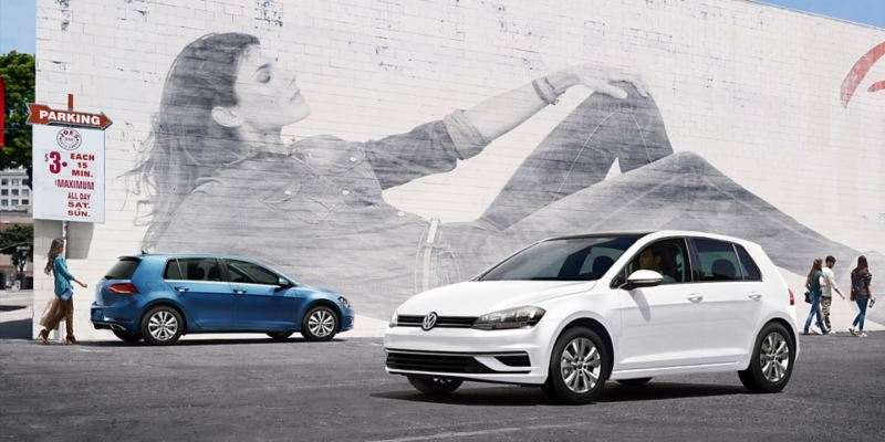 Pure White Volkswagen Golf parked in a parking lot by a large mural of a woman laying down