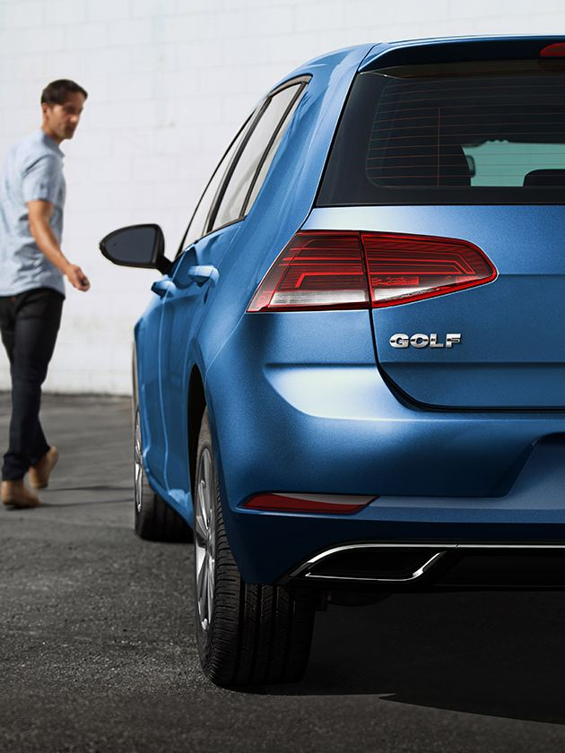 A man walks away from a VW Golf in Silk Blue Metallic using his key fob to lock the door, as seen from the rear driver side.