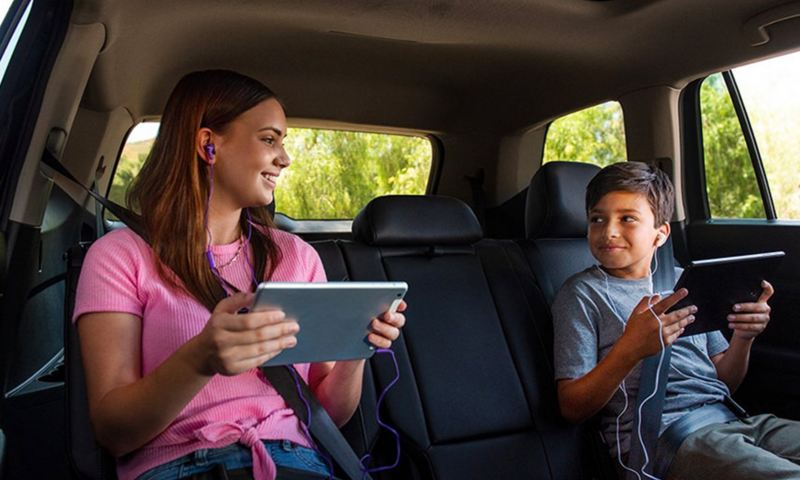 Two children enjoy using the VW Car-Net Hotspot with their wireless tablets in the second row.