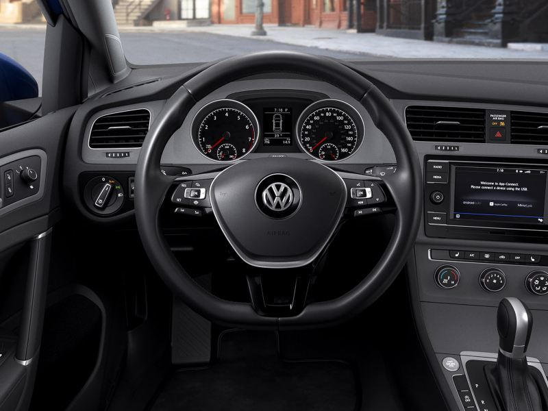 A view of the steering wheel from the driver's seat in a Volkswagen Golf.