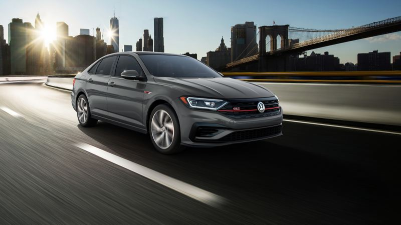 Jetta GLI in Pure Gray driving away from the city. Color adds an additional $295 to price of car.
