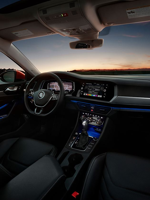 A driver's view of the Jetta interior in available Titan Black leather seen at night.