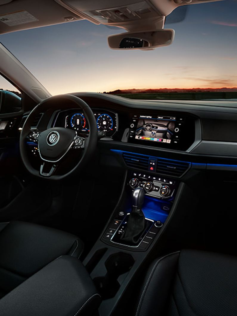 Jetta interior in available Titan Black leather seen at night.