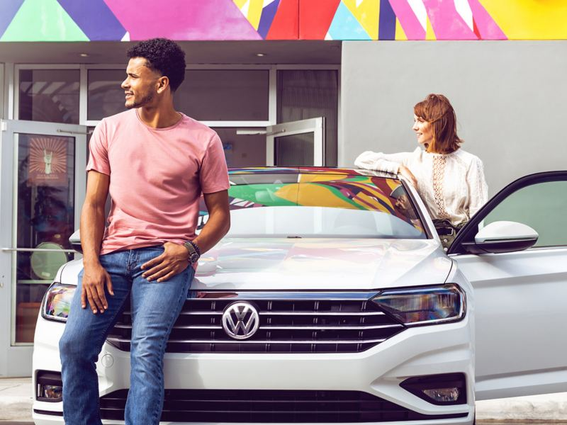 Jetta shown in Pure White as seen from the front parked with a man leaning on the hood and a woman standing with the driver's door open.