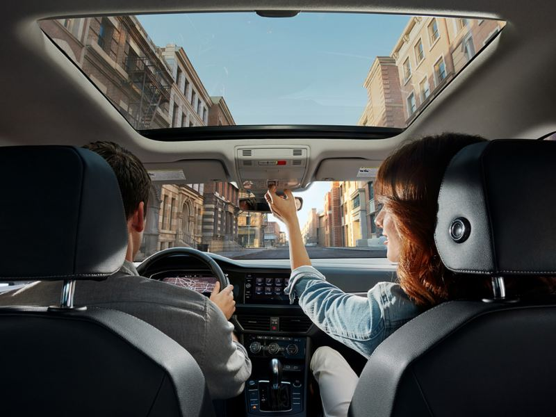 Available panoramic sunroof in use by a couple seated in the front seats.