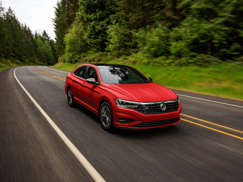 Jetta shown in Tornado Red as seen from the front driving on a road with trees in the background.