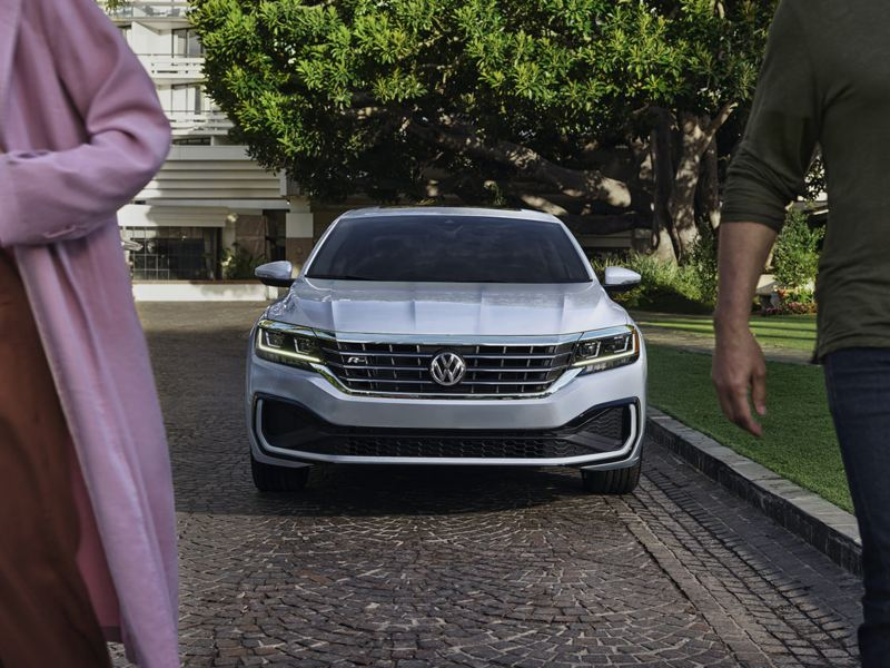 Exterior front view of a Passat in Reflex Silver Metallic parked next to a lawn with driver and passenger walking away