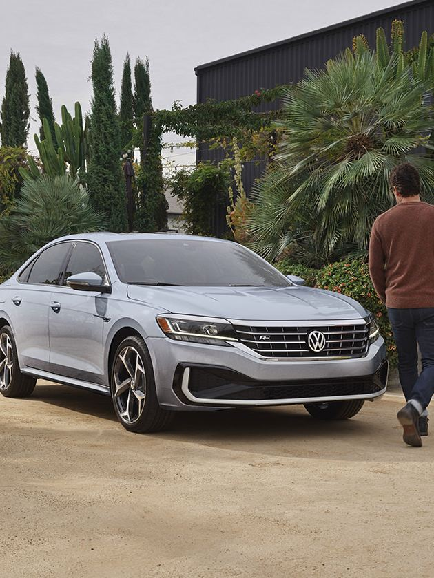 Exterior front view of a Passat in Reflex Silver Metallic with the driver walking in front