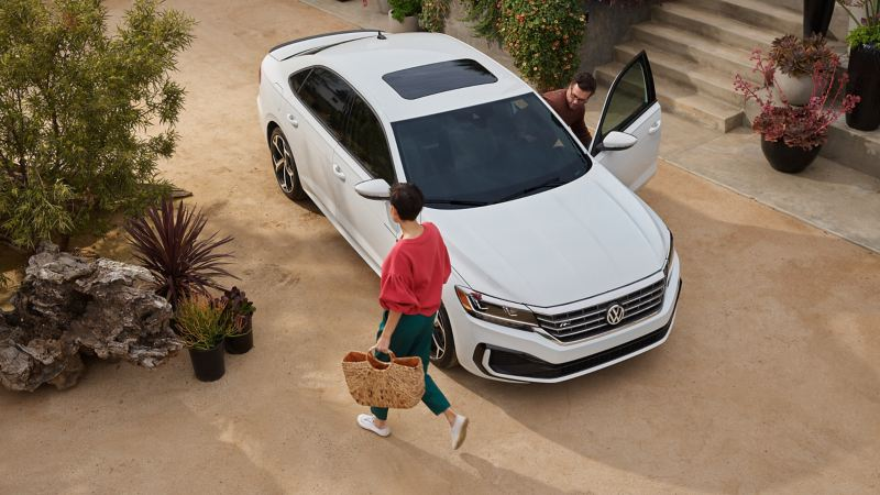 Aerial view of a man and woman getting into a VW Passat.