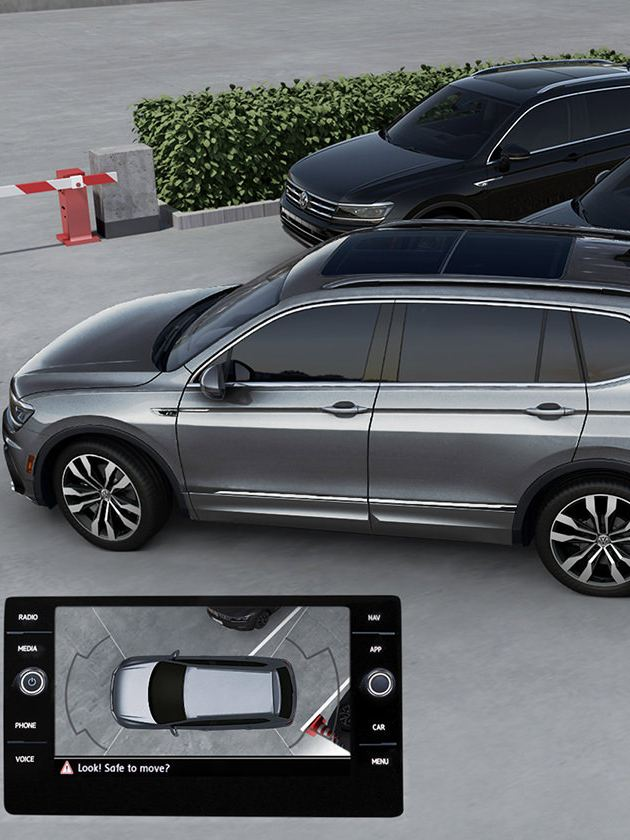 A Platinum Gray Metallic Tiguan backing into a parking space with a smaller image of the infotainment screen showing that as well