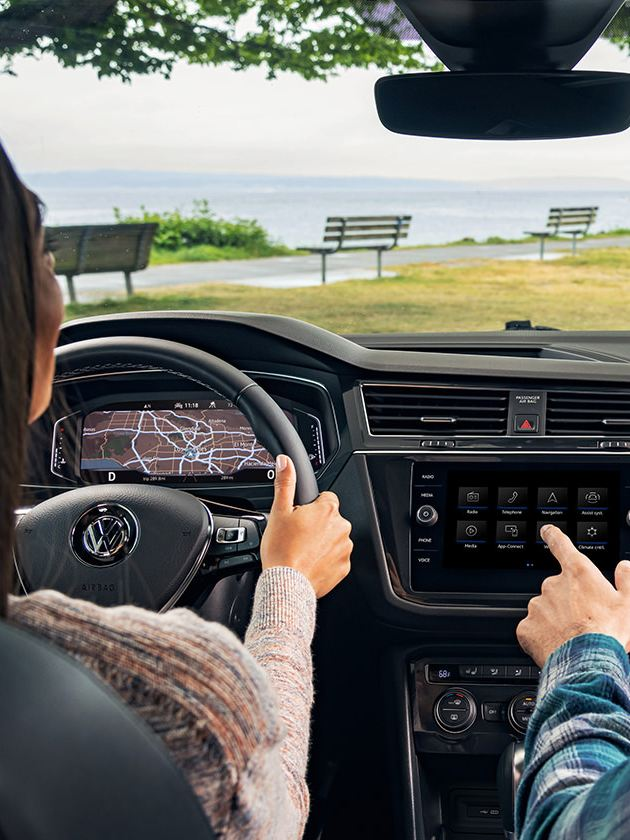 """The available Volkswagen Digital Cockpit and 8"""" touchscreen navigation system in use by a couple seated in the front seats."""