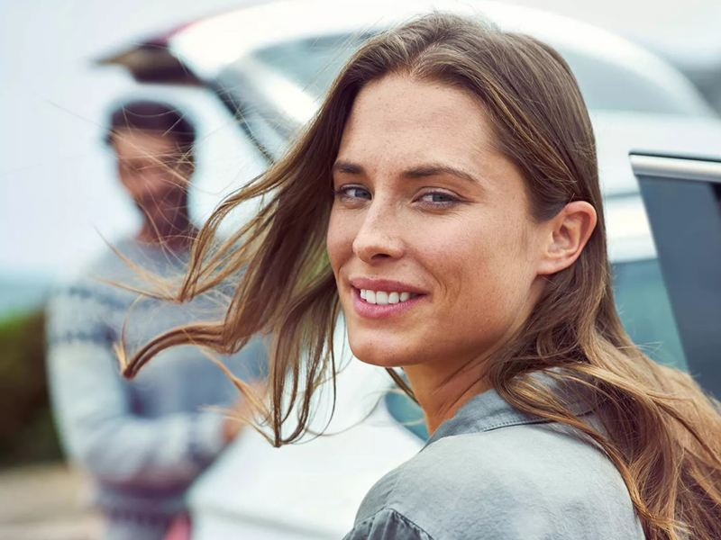A woman smiles for the camera in front of a Volkswagen with the trunk open and a man standing behind it.