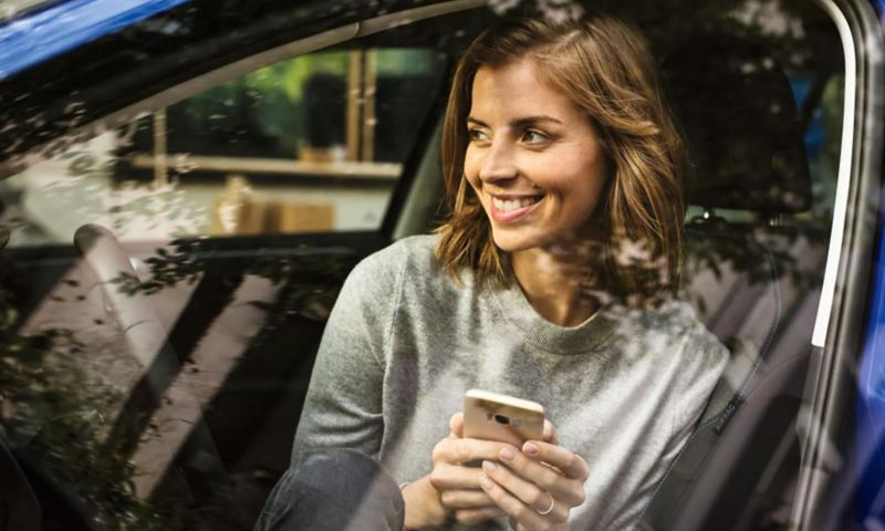 Smiling woman sits in the front seat of a parked VW, smartphone in hand.